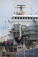 Visitors stand along the viewing platform at Lock 3 at the St Catharines Museum in Ontario, Canada watching a large bulk carrier.