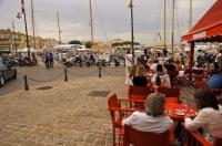 People relaxing at a street cafe in St. Tropez in the Var region of Provence in France, Europe.