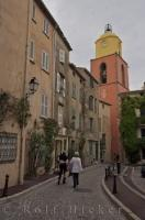 The colourful bell tower of the Eglise Notre Dame can be seen at the end of the the Rue Saint Jean, which is a narrow winding street in the Old Town of St Tropez in The Var, a department in the beautiful Provence, France.
