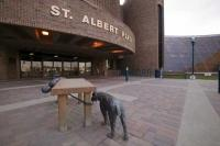 A cute bronze sculpture of a boy and dog outside the City Hall Building in St Albert, Alberta, Canada.