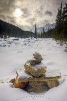 A stone cairn sits on the banks of the Mistaya River and is covered in a light dusting of snow after a fresh snow fall over the Canadian Rocky Mountains. This winter scenery picture shows the Mistaya Canyon and Mount Sarbach in the background.
