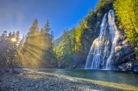Sun beams striking through the rainforest  onto a beautiful wilderness waterfall on the west coast of Vancouver Island, British Columbia, Canada.