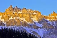 The jagged peaks of the mountain, aptly named Dolomite Peak, rise up to 2,782 metres and are part of the Canadian Rocky Mountains in Banff National Park. The sunlit peaks glow as the sun sets for another day.