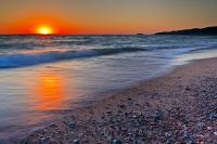 Sitting along the shore of Agawa Bay in Lake Superior Provincial Park in Ontario, Canada watching a stunning sunset is a relaxing way to spend an evening.