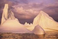 A beautiful pink sunset reflects of this large iceberg in Notre Dame Bay near Twillingate in Newfoundland, Canada.