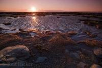 At sunset along the shores of the St Lawrence River in Quebec, the beautiful light dances across the low tide banks.