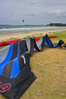 A surfing kite lays to rest on Orewa Beach, just north of Auckland, on the North Island of New Zealand, while others are already sailing.