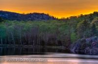 The surreal colour of sunset turns the sky to various shades of yellow high above the trees and still waters of George Lake in Killarney Provincial Park; a popular park in Ontario, Canada. The beautiful landscapes of this area attract many artists.