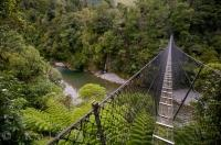 The Waiohine River has carved out a deep gorge where a swing bridge forms a gateway to the Tararua Forest Park in New Zealand.