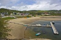 The wide, sandy beach in the village of Tadoussac in Quebec, Canada forms a semi-circle around the water's edge and the marina.