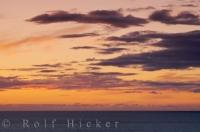 The colorful sky over the Tasman Sea seen from the shores of the North Taranaki Bight on the North Island of New Zealand during the sunset hours.