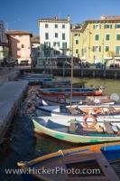 The Lake Garda waterfront in the town of Torbole in the Province of Trento, Italy is adorned with small boats of various colors.
