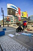 A man creates an artwork picture in chalk on the street in Yonge-Dundas Square in the downtown core of Toronto, Ontario in Canada.