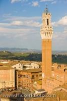 An aerial view of Piazza del Campo shows how the Torre del Mangia in Siena, Tuscany in Italy towers above the rooftops of the city and the surrounding landscape.