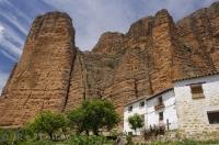 Towering walls of rock known as Los Mallos de Riglos, dwarf the white houses in the village of Riglos in Huesca, Aragon in Spain, Europe.