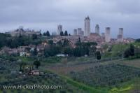 Multiple towers dominate the skyline in the medieval town of San Gimignano as seen from a distance, which is located in the Siena Province, in Tuscany Italy.