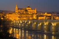 The Puente Romano spanning the Rio Guadalquivir in the province of Cordoba in Andalusia, Spain, is lit up at dusk with the Mezquita (Cathedral-Mosque) lit strikingly in the background. Cordoba is a popular tourist destination in Andalusia, Spain.