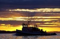 A commercial tug boat is highlighted by a gorgeous sunset off Northern Vancouver Island in British Columbia, Canada.