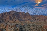 The moon shines brightly behind a series of cloud formations above the Sierra Nevada Mountain range and above the surreal scenery and rock formations of the Alabama Hills at twilight.