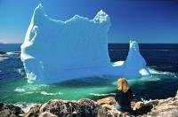 A woman sits on the rocks in the village of Twillingate, Newfoundland in Canada where an iceberg has beached itself.