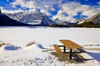 A picnic table which sits along the shore of the snow covered Upper Kananaskis Lake is surrounded by beautiful winter scenery. The Kananaskis mountain range is a beautiful backdrop to the lake.