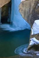 During the winter in the Wildgerlos Valley in the Salzburger Land of Austria, Europe, the Leitenkammerklamm waterfall becomes partly frozen but still has flowing water underneath a sheet of ice.