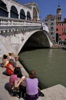 Visitors to Venice bath in the hot afternoon sun beside the Rialto Bridge and Grand Canal.