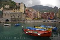 Quaint fishing boats line the waterfront in the pretty village of Vernazza, Liquria, Italy.