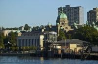 A mix of historic and modern buildings line the inner harbour in the city of Victoria, BC, Canada.