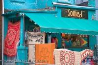 A turquoise colored Victorian styled building prominently stands out near the Kensington Market in Toronto, Ontario where a unique shop is located.