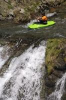 A kayaking enthusiast paddles up to the brink of the waterfall in the Pyrenees, Catalonia, Spain.
