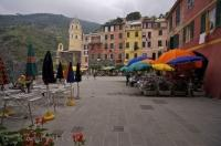 The colourful umbrellas of the waterfront cafes in the village of Vernazza in the Cinque Terre region of Liguria, Italy, in Europe.