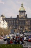 People and vehicles swarm the street near Wenceslas Square in downtown Prague in the Czech Republic as the historic National Museum towers over them.