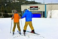 At this Whistler Mountain Ski School in British Columbia, a ski instructor teaches and helps a student with their ski skills. Whistler is known as a first-class destination for skiing and winter sports and is soon to co-host the Olympics.