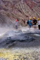 Passengers who boarded the boat tour to White Island, New Zealand enjoy the opportunity of standing around large volcanic openings found in the landscape.