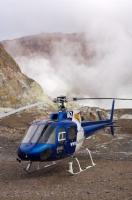 A helicopter with passengers aboard a tour, lands on an active volcano known as White Island in the Bay of Plenty in New Zealand.