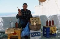 A wine vendor sitting in the shade of a treeing selling wine in Pyrgos Santorini Greece.