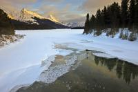 A beautiful scenic view of the partially frozen Maligne River and Maligne Lake leading back towards the landscape of the snow-capped mountains during winter in Jasper National Park.