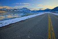 A paved road leads towards a beautiful winter wonderland in the Rocky Mountains inside the Waterton Lakes National Park in southern Alberta