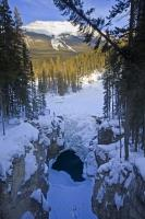 During the winter months the Sunwapta Falls along the Icefields Parkway in Jasper National Park in the Rocky Mountains, are covered in snow and ice and surrounded by stupendous winter scenery.