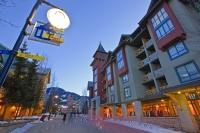A picture of the plaza of Whistler Village in winter as people walk along the Village Stroll at dusk.