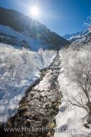 The sunlight sparkles across the winter wilderness of the Wildgerlos Valley in Austria, Europe as the river finally begins to melt and trickle over the rocks.
