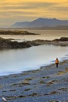 A woman takes a walk after sunset along South Beach located in the Long Beach Unit of the Pacific Rim National Park - part of the Clayoquot Sound UNESCO Biosphere Reserve. This park can be found on the West Coast of Vancouver Island in British Columbia.