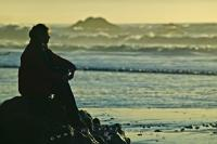 The silhouette of a woman sitting on a rock on Ruby Beach in the Olympic National Park, Olympic Peninsula of Washington, USA.
