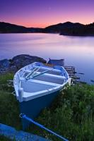 A wooden fishing boat resting on the shore at twilight in the small town of Fleur de Lys in Newfoundland, Canada is a peaceful sight.