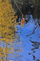 Zipling in the winter is an exhilarating experience as you whiz through the tree tops at high speeds. This person is ziplining across the Fitzsimmons Creek between Whistler and Blackcomb Mountains with Ziptreck Ecotours in Whistler, British Columbia.