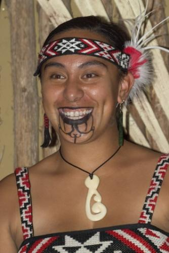 A Maori woman proudly shows her tattoo designs and maori symbols.