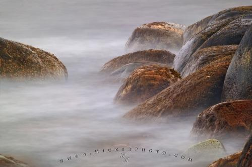 Long exposure photo of a ocean wave crashing against rocks