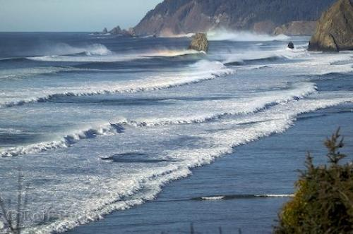 A field of ocean waves force their way into shore at Cannon Beach against