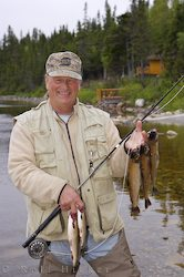 photo of a fisher man with trout fish in his hand